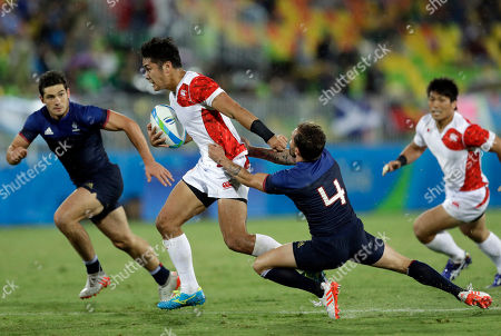Stock Image of Japan's Teruya Goto, second from left, avoids a tackle from France's Terry Bouhraoua, second from right, during the men's rugby sevens match at the Summer Olympics in Rio de Janeiro, Brazil