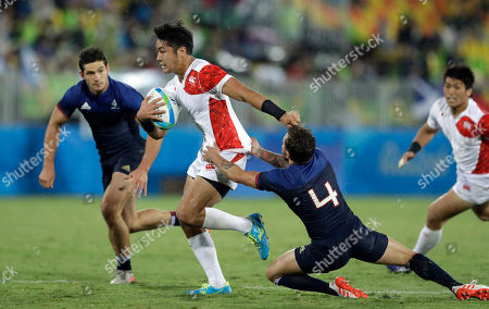 Japan's Teruya Goto, middle, avoids a tackle from France's Terry Bouhraoua, right, during the men's rugby sevens match at the Summer Olympics in Rio de Janeiro, Brazil
