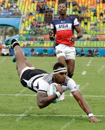 Fiji's Semi Kunatani, front, scores a try as United States's Perry Baker, watches during the men's rugby sevens match at the Summer Olympics in Rio de Janeiro, Brazil
