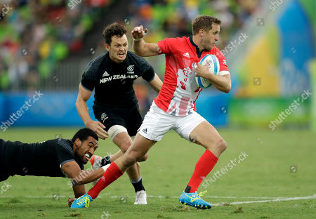 Britain's Mark Robertson, right, is challenged by New Zealand's Sione Molia, left, and teammate Lewis Ormond, during the men's rugby sevens match at the Summer Olympics in Rio de Janeiro, Brazil