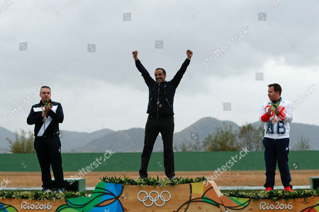 Fehaid Aldeehani, center, an independent athlete from Kuwait competing on the Refugee Olympic Team celebrates winning the gold medal as silver medalist Marco Innocenti of Italy, left, and bronze medalist Steven Scott of Britain clap during the victory ceremony for the men's double trap event, at the Olympic Shooting Center at the 2016 Summer Olympics in Rio de Janeiro, Brazil