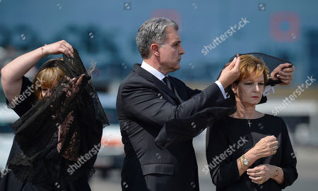 Princess Margaret, right, daughter of Romania's last monarch King Michael, stands as her husband Prince Radu of Romania, center, adjusts her scarf, before a religious service as the body of Anne of Romania arrives in Otopeni, Romania, . The body of Anne of Romania, the wife of the country's ex-king, arrived in Bucharest Tuesday for the biggest royal funeral in almost 80 years