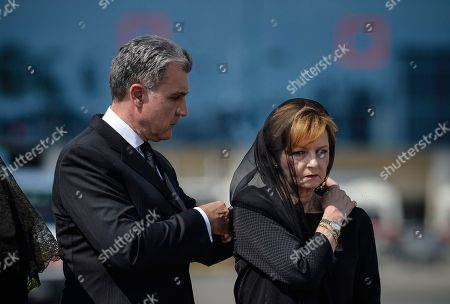Princess Margaret, right, daughter of Romania's last monarch King Michael, stands as her husband Prince Radu of Romania adjusts her scarf, before a religious service as the body of Anne of Romania arrives in Otopeni, Romania, . The body of Anne of Romania, the wife of the country's ex-king, arrived in Bucharest Tuesday for the biggest royal funeral in almost 80 years