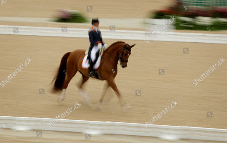 With a slow shutter speed, Netherlands' Adelinde Cornelissen, riding Parzival, competes in the equestrian dressage competition at the 2016 Summer Olympics in Rio de Janeiro, Brazil