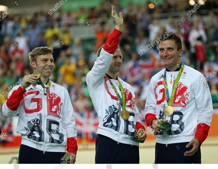 Great Britain gold medalists, from left, Philip Hindes, Jason Kenny, and Callum Skinner, right, pose on the podium of the men's team sprint finals at the Rio Olympic Velodrome during the 2016 Summer Olympics in Rio de Janeiro, Brazil, Thursday, Aug. 11, 2016