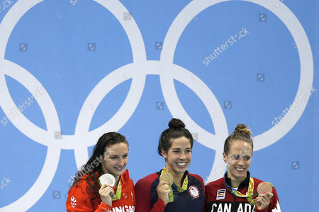 Stock Picture of Hungary's Katinka Hosszu, United States' Maya DiRado, Canada's Hilary Caldwell, from left, hold up their medals in the women's 200-meter backstroke medals ceremony during the swimming competitions at the 2016 Summer Olympics, Friday, Aug. 12, 2016, in Rio de Janeiro, Brazil.