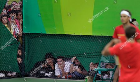 Rafael Nadal, Marc Lopez Fans peer through chain link fencing to watch Rafael Nadal and Marc Lopez, of Spain, play men's doubles against Daniel Nestor and Vasek Pospisil, of Canada, on a smaller outer court, which was filled to capacity, at the 2016 Summer Olympics in Rio de Janeiro, Brazil