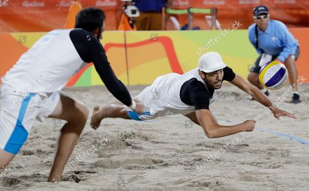 Paolo Nicolai, left, watches his teammate Daniele Lupo diving for a ball during a men's beach volleyball round of 16 match against their compatriots Alex Ranghieri and Adrian Carambula Raurich