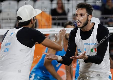 Paolo Nicolai, right, and his teammate Daniele Lupo, left, celebrate winning a point during a men's beach volleyball round of 16 match against their compatriots Alex Ranghieri and Adrian Carambula Raurich