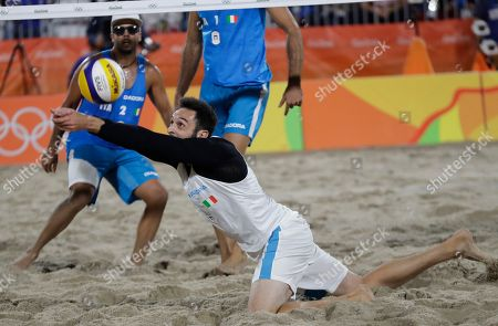 Paolo Nicolai stretches for a ball during a men's beach volleyball round of 16 match against his compatriots Alex Ranghieri and Adrian Carambula Raurich
