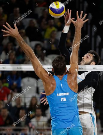 Italy's Alex Ranghieri, left, tries to block his compatriot Paolo Nicolai, right, during a men's beach volleyball round of 16 match