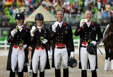 From left, Britain's Fiona Bigwood, Charlotte Dujardin, Carl Hester and Spencer Wilton celebrate after winning the silver medal in the equestrian dressage team competition at the 2016 Summer Olympics in Rio de Janeiro, Brazil