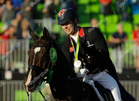Britain's Spencer Wilton, riding Super Nova II, celebrates after his team won silver in the equestrian dressage team competition at the 2016 Summer Olympics in Rio de Janeiro, Brazil