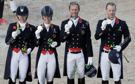 Silver medal winners Britain's Fiona Bigwood, left, Charlotte Dujardin, second left, Carl Hester, second right, and Spencer Wilton, right, after the team dressage equestrian competition at the 2016 Summer Olympics in Rio de Janeiro, Brazil