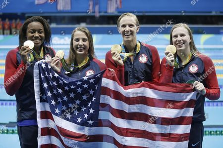 From right to left, United States' Lilly King, Dana Vollmer, Kathleen Baker and Simone Manuel display their gold medals for the women's 4 x 100-meter medley relay final during the swimming competitions at the 2016 Summer Olympics, Saturday, Aug. 13, 2016, in Rio de Janeiro, Brazil.