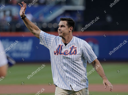 Former Major League Baseball player Billy Bean waves to baseball fans after throwing out the first pitch before the start of a baseball game between the New York Mets and the San Diego Padres, in New York. Bean threw out the pitch on the first Mets Pride Night