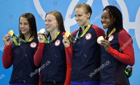 From left to right, United States' Kathleen Baker, Lilly King, Dana Vollmer and Simone Manuel display their gold medals for the women's 4 x 100-meter medley relay final during the swimming competitions at the 2016 Summer Olympics, in Rio de Janeiro, Brazil