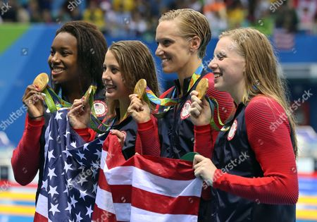 From right to left, United States' Lilly King, Dana Vollmer, Kathleen Baker and Simone Manuel display their gold medals for the women's 4 x 100-meter medley relay final during the swimming competitions at the 2016 Summer Olympics, in Rio de Janeiro, Brazil