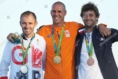 Netherlands' gold medalist Dorian van Rijsselberghe, center, Britain's silver medalist Nick Dempsey, left, and France's bronze medalist Pierre Le Coq stand on the podium during the medals ceremony for the RS: X men's windsurfing event at the Summer Olympics in Rio de Janeiro, Brazil, Sunday, Aug. 14, 2016.