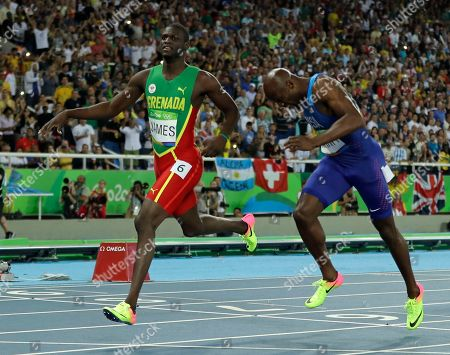 Grenada's Kirani James, left, and United States' Lashawn Merritt cross the line of the men's 400-meter final during the athletics competitions in the Olympic stadium of the 2016 Summer Olympics in Rio de Janeiro, Brazil
