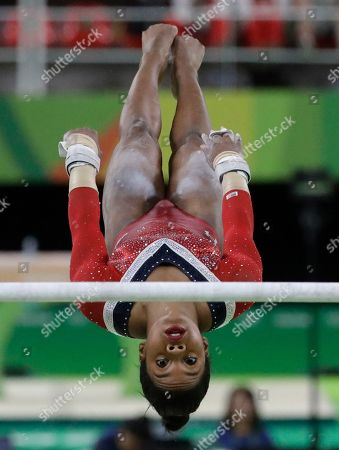 Stock Picture of United States' Gabrielle Douglas performs on the uneven bars during the artistic gymnastics women's apparatus final
