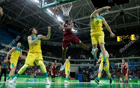 Venezuela's Miguel Ruiz, center, drives to the basket between Australia's Andrew Bogut (6) and Damian Martin (15) during a basketball game