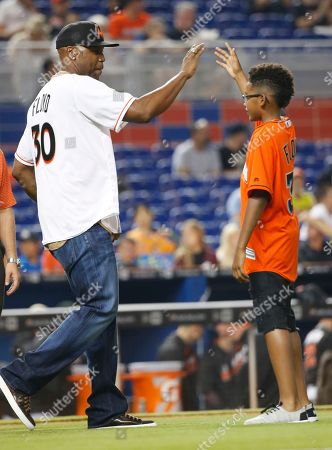 Stock Picture of Cliff Floyd, Tobias Floyd Former Florida Marlins' Cliff Floyd, left, celebrates after catching a ceremonial first pitch thrown out by his son Tobias, right, before the start of a baseball game between the Miami Marlins and the Chicago White Sox, in Miami