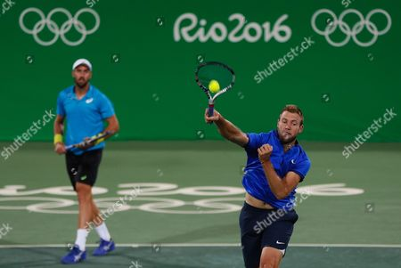 Jack Sock, right, and Steve Johnson of the United States return to Canada's Vasek Pospisil and Daniel Nestor in the men's doubles tennis competition at the 2016 Summer Olympics in Rio de Janeiro, Brazil