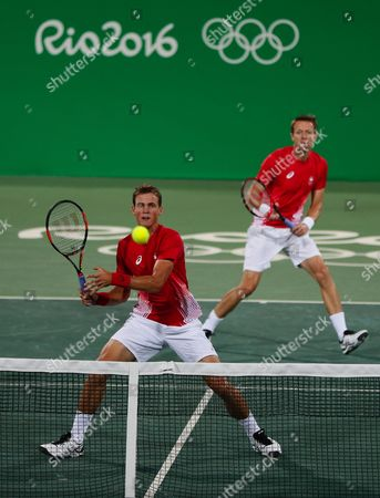 Canada's Vasek Pospisil and Daniel Nestor, right, return to Jack Sock, and Steve Johnson of the United States return in the men's doubles tennis competition at the 2016 Summer Olympics in Rio de Janeiro, Brazil