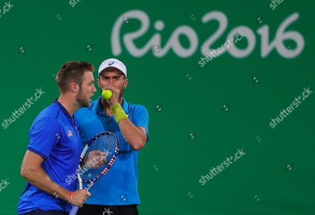 Jack Sock, left, and Steve Johnson of the United States speak during the match against Canada's Vasek Pospisil and Daniel Nestor in the men's doubles tennis competition at the 2016 Summer Olympics in Rio de Janeiro, Brazil