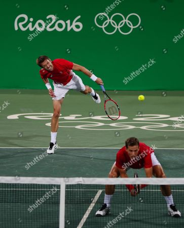 Canada's Vasek Pospisil and Daniel Nestor, right, serve to Jack Sock, and Steve Johnson of the United States return in the men's doubles tennis competition at the 2016 Summer Olympics in Rio de Janeiro, Brazil