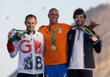 Netherlands' gold medalist Dorian van Rijsselberghe, center, Britain's silver medalist Nick Dempsey, left, and France's bronze medalist Pierre Le Coq stand on the podium during the medals ceremony for the RS: X men's windsurfing event at the Summer Olympics in Rio de Janeiro, Brazil