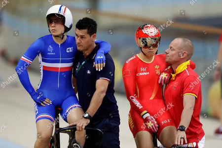 Gong Jinjie of China, right, and Sandie Clair of France, left, wait with their coaches to compete in the women's Keirin first round cycling repechage at the Rio Olympic Velodrome during the Summer Olympics in Rio de Janeiro, Brazil