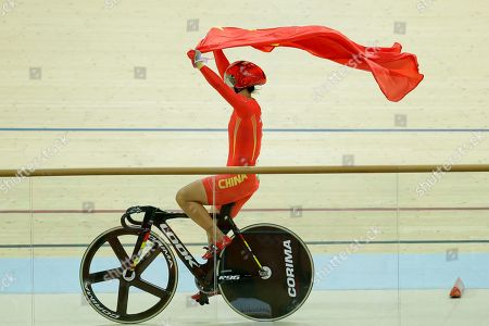 Jinjie Gong of China waves her country's national flag after winning gold with teammate Tianshi Zhong in the Women's team sprint finals at the Rio Olympic Velodrome during the 2016 Summer Olympics in Rio de Janeiro, Brazil