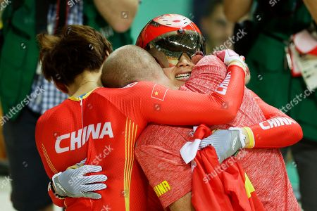 Jinjie Gong, right, and teammate Tianshi Zhong, left, of China hug with coach Benoit Vetu, center, after winning gold in the Women's team sprint finals at the Rio Olympic Velodrome during the 2016 Summer Olympics in Rio de Janeiro, Brazil