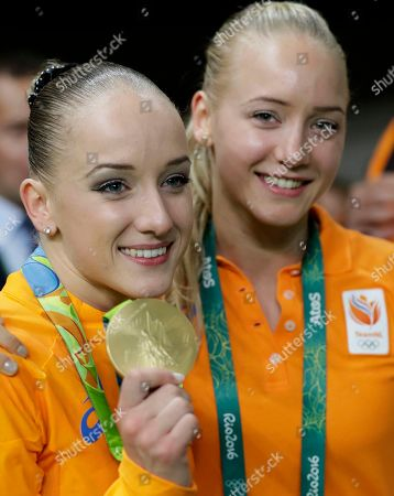 Netherlands' Sanne Wevers displays her gold medal for balance beam, as twin sister Lieke stands by her side during the artistic gymnastics women's apparatus final at the 2016 Summer Olympics in Rio de Janeiro, Brazil