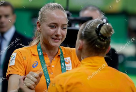 Netherlands' Sanne Wevers, back to camera, is congratulated by her twin sister Lieke for winning gold in balance beam during the artistic gymnastics women's apparatus final at the 2016 Summer Olympics in Rio de Janeiro, Brazil