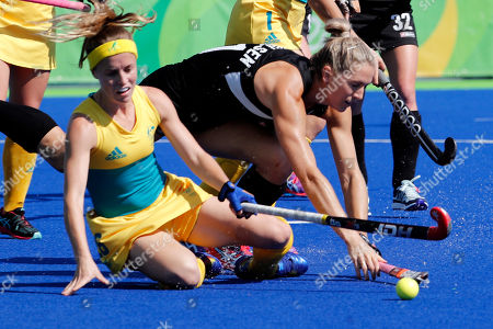 Australia's Emily Smith, left, fights for the ball with New Zealand's Stacey Michelsen during a women's field hockey quarter final match at the 2016 Summer Olympics in Rio de Janeiro, Brazil