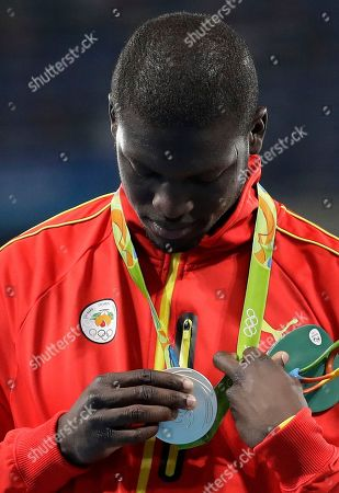 Grenada's Kirani James looks at his silver medal during the medal ceremony for the men's 400-meter final during the athletics competitions of the 2016 Summer Olympics at the Olympic stadium in Rio de Janeiro, Brazil