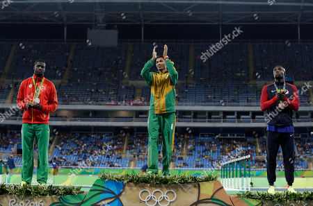 South Africa's gold medal winner Wayde Van Niekerk is flanked by Grenada's silver medal winner Kirani James, left, and United States' bronze medal winner Lashawn Merritt during the medal ceremony for the men's 400-meter final during the athletics competitions of the 2016 Summer Olympics at the Olympic stadium in Rio de Janeiro, Brazil