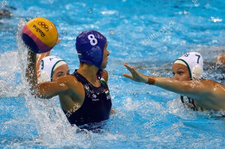 Hungary's Rita Keszthelyi, left, passes the ball forward as Australia's Rowie Webster, right, goes to block during their women's water polo quarterfinal round match at the 2016 Summer Olympics in Rio de Janeiro, Brazil
