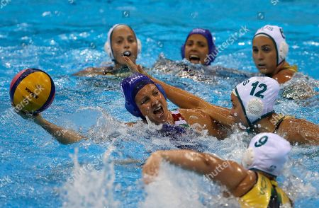 Stock Photo of Hungary's Ildiko Toth, left, passes the ball forward as Australia's Nicola Zagame, right, goes to block during their women's water polo quarterfinal round match at the 2016 Summer Olympics in Rio de Janeiro, Brazil