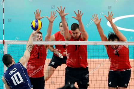 Italy's Filippo Lanza (10) spikes the ball as from the left, Canada's Tyler Sanders, Gavin Schmitt, Graham Vigrass, and Nicholas Hoag block during a men's preliminary volleyball match at the 2016 Summer Olympics in Rio de Janeiro, Brazil