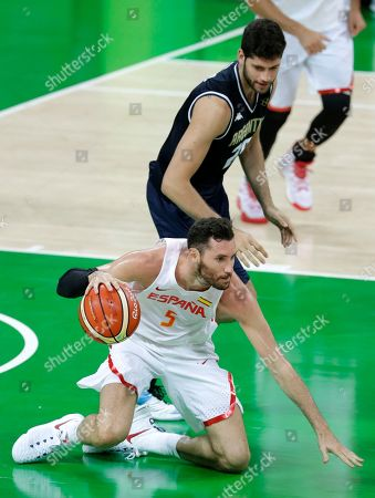 Spain's Rudy Fernandez (5) falls to the court in front of Argentina's Patricio Garino during a basketball game