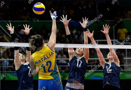 Brazil's Natalia Pereira spikes the ball against China's Wei Qiuyue, left, Yan Ni, and Hui Ruoqi in a women's quarterfinal volleyball match at the 2016 Summer Olympics in Rio de Janeiro, Brazil