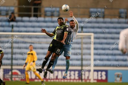Bury midfielder Tom Soares (19) and Coventry City forward Marcus Tudgay (20) battle for the header during the EFL Sky Bet League 1 match between Coventry City and Bury at the Ricoh Arena, Coventry