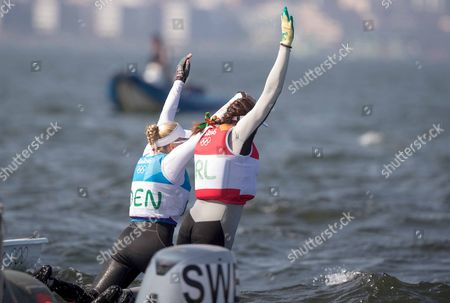 Sailing - Women?s Laser Radial Medal Race. Ireland's Annalise Murphy celebrates winning a silver medal with bronze medalist Anne-Marie Rindom from Denmark by jumping into the sea