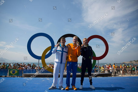 Gold medalist Ferry Weertman, of the Netherlands, center, poses for photos with silver medalist Spyridon Gianniotis, of Greece, left, and bronze medalist Marc-Antoine Olivier, of France, after the men's marathon swimming competition at the 2016 Summer Olympics in Rio de Janeiro, Brazil