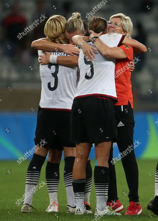 Germany coach Silvia Neid, right, embraces Annike Krahn at the end of a semi-final match of the women's Olympic football tournament between Canada and Germany at the Mineirao stadium in Belo Horizonte, Brazil, . Germany won 2-0 and qualified to the final
