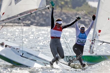 Second placed Ireland's Annalise Murphy, left, and third placed Denmark's Anne-Marie Rindom jump into the water at the end of the Laser Radial Women event during the 2016 Summer Olympics in Rio de Janeiro, Brazil
